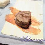mettiamo la pasta sfoglia, poi il prosciutto, la crema di funghi e il pezzo di carne.